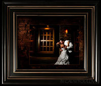 bride and groom kiss under window light