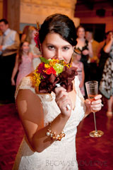 journalistic photograph of a happy bride just before tossing her flower boquet