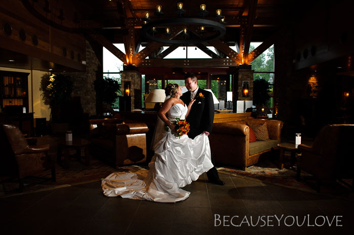 The bride and groom embrace in the lobby of a ski lodge.
