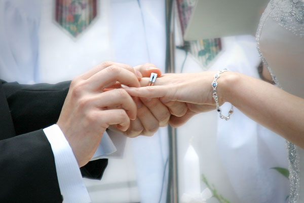 the bride and groom exchange rings in this photograph